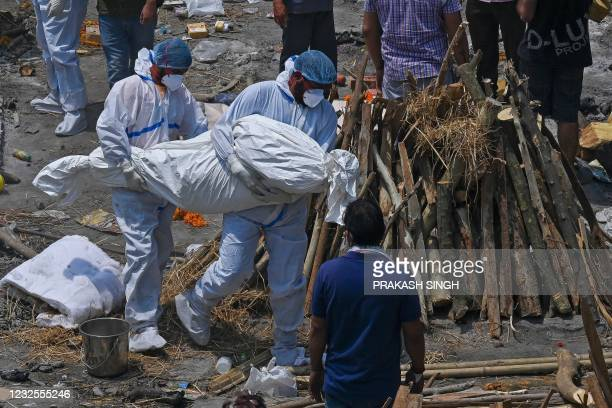 Family members and ambulance worker wearing PPE kit carry the bodies of the patients who died of the Covid-19 coronavirus at a cremation ground in...