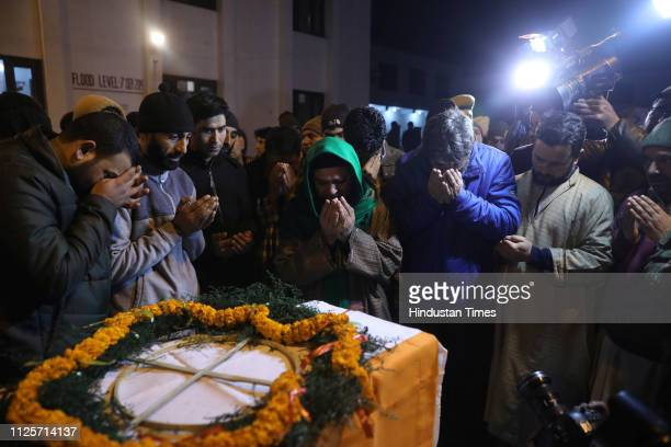 Family members and colleagues of a police man who was killed in a gun battle in Pulwama pray near his coffin during a wreathlaying ceremony on...