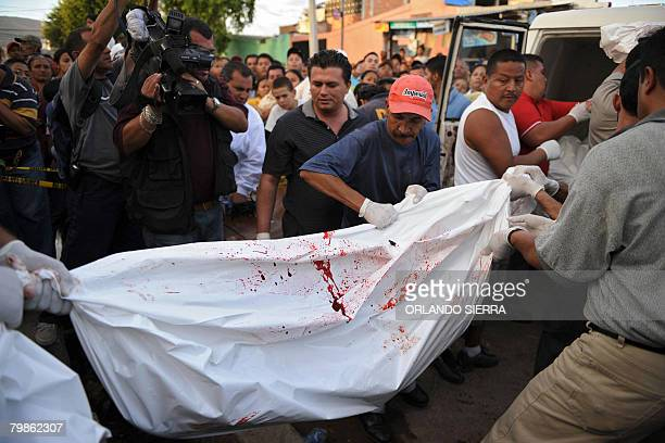 Family members and friends carry plastic bags containing the corpses of a family murdered in their home in the northern outskirts of Tegucigalpa on...