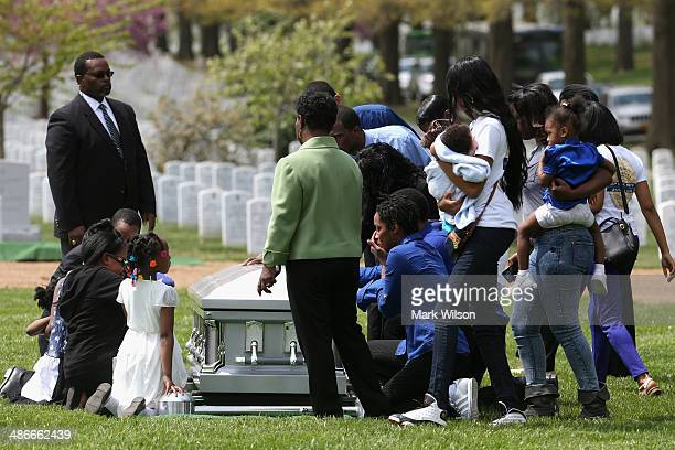 Family members and friends gather around the casket of Navy MasteratArms 2nd Class Mark Mayo during a burial service at Arlington Cemetery on April...