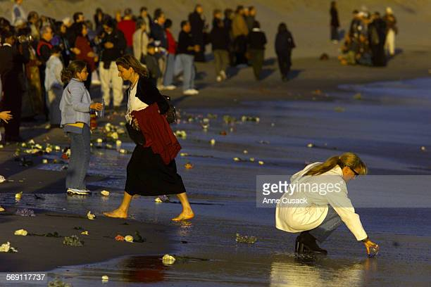 Family members and friends of Alaska Airlines Flight 261 crash victims gather sand from the beach after tossing flowers into the ocean at the...