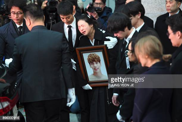 TOPSHOT Family members and friends of late SHINee singer Kim JongHyun cry as they carry out his coffin during a funeral at a hospital in Seoul on...