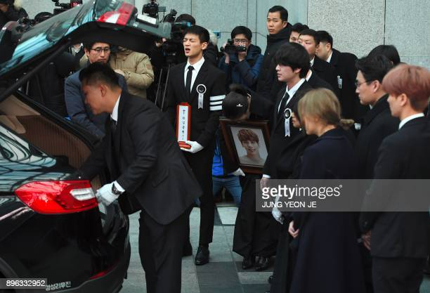 Family members and friends of late SHINee singer Kim JongHyun cry as they carry out his coffin during a funeral at a hospital in Seoul on December 21...