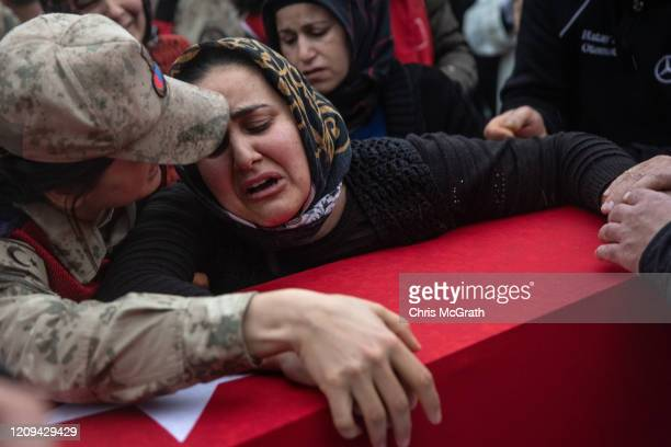 Family members and friends of Turkish soldier Emin Yildirim who was killed in an airstrike in Idlib on February 27 mourn over his coffin during his...