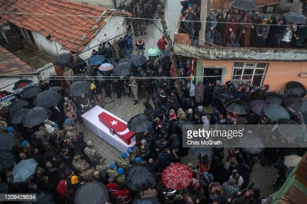 Family members and friends of Turkish soldier Emin Yildirim who was killed in an airstrike in Idlib on February 27 gather around his coffin during...