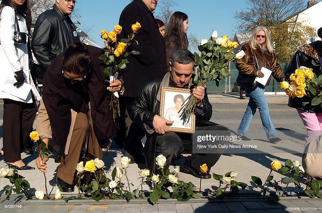 Family members and friends place roses along the sidewalk in : News Photo