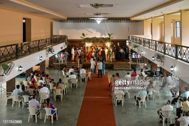 Family members and guests of the bride and the groom seated in a marriage hall watch the rituals during a traditional Hindu wedding, after the...