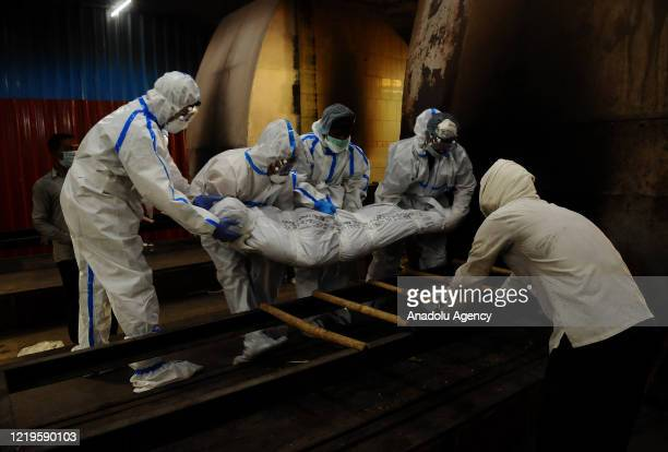 Family members and health workers move the body of a person who died due to coronavirus on to a cart for cremation at Nigambodh Ghat crematorium in...