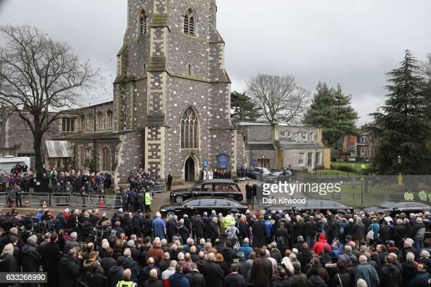 Family members and mourners look on as the hearse carrying the coffin of former England Football Team Manager Graham Taylor arrives ahead of his...