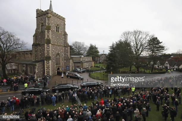 Family members and mourners look on as the hearse carrying the coffin of former England Football Team Manager Graham Taylor prepares to leave after...