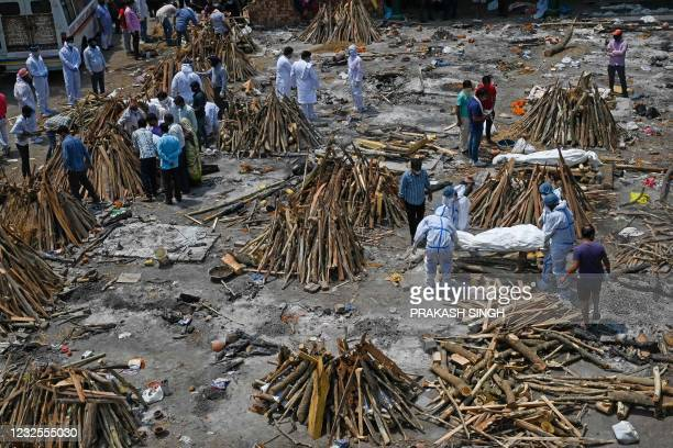 Family members and relatives prepare the funeral pyre of victims who died of the Covid-19 coronavirus during mass cremation held at a crematorium in...