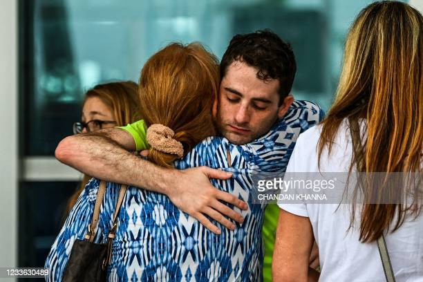 Family members and residents of the Champlain Towers South greet each other outside the Town of Surfside Community Center in Surfside, north of Miami...