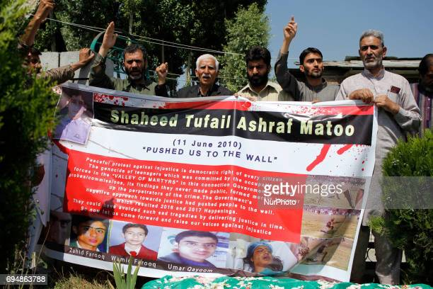 Family members and the proindependence group leaders hold a banner as they shout profreedom slogans in front of the Grave of Tufail Matoo 17 year old...