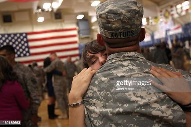 Family members and US soldiers embrace following a welcome home ceremony for troops returning from Iraq on November 10 2011 in Fort Carson Colorado...