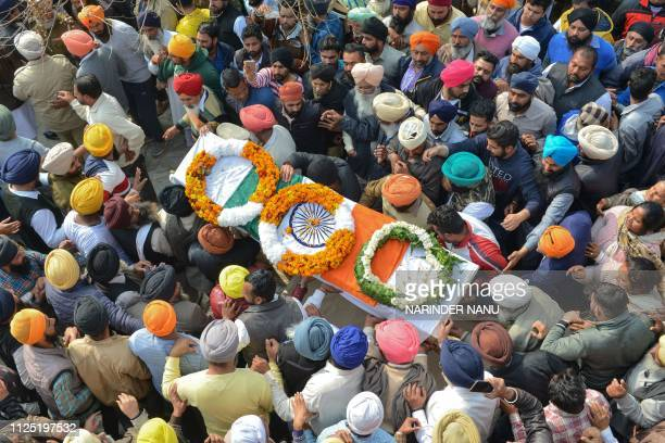 Family members and villagers carry the coffin of Indian Central Reserve Police Force trooper Sukhjinder Singh during the cremation ceremony at...