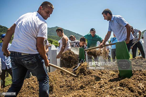 Family members and volunteers bury one of the 136 coffins of newlyidentified victims of the 1995 Srebrenica massacre into its final grave mass...