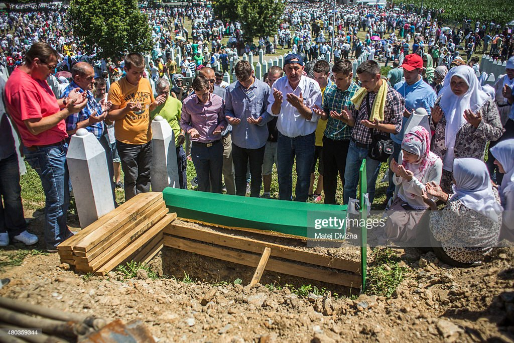 Family members and volunteers pray over one of the 136 coffins of newly-identified victims of the 1995 Srebrenica massacre next to its final grave during the 20th anniversary of the massacre at the Potocari cemetery and memorial on July 11, 2015 in Srebrenica, Bosnia and Herzegovina. At least 8300 Bosnian Muslim men and boys who had sought safe heaven at the U.N.-protected enclave at Srebrenica were killed by members of the Republic of Serbia (Republika Srpska) army under the leadership of General Ratko Mladic, who is currently facing charges of war crimes at The Hague, during the Bosnian war in 1995.