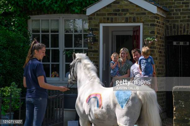 Family members Bryony Alice , who's 2nd birthday it is today, Stanley and Paul Blant , stand on their doorstep looking at a Welsh mountain pony...