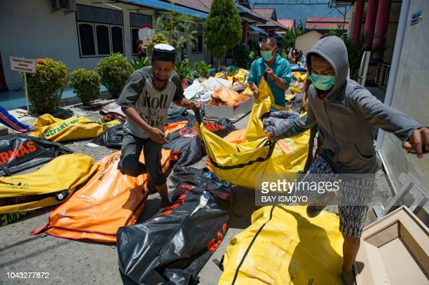 TOPSHOT Family members carry the body of a relative to the compounds of a police hospital in Palu Indonesia's Central Sulawesi on September 30...