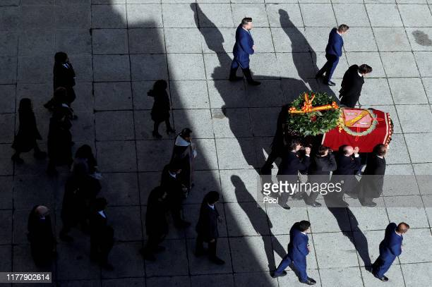 Family members carry the coffin of Francisco Franco out of the basilica of the Valley of the Fallen mausoleum to a hearse during the exhumation of...