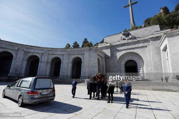Family members carry the coffin of Francisco Franco out of the basilica of the Valley of the Fallen mausoleum into a hearse for transportation during...