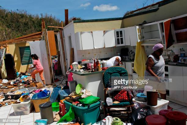 TOPSHOT Family members collect belongings after hurricane force winds destroyed their house in Toa Baja west of San Juan Puerto Rico on September 24...