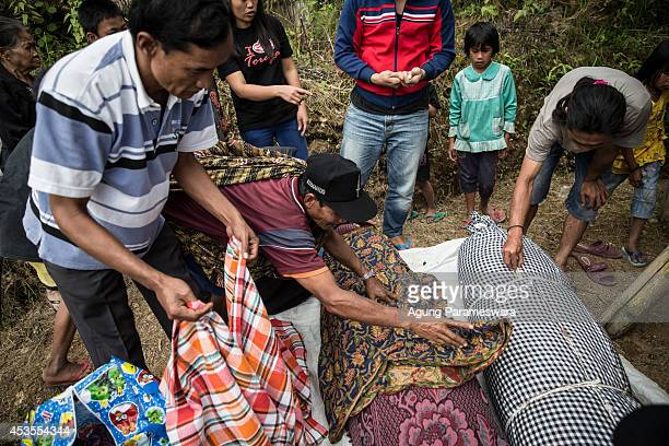 Family members cover a body of deceased by cloth during Manene ritual on August 13 2014 in Toraja South Sulawesi Indonesia The Manene ritual involves...