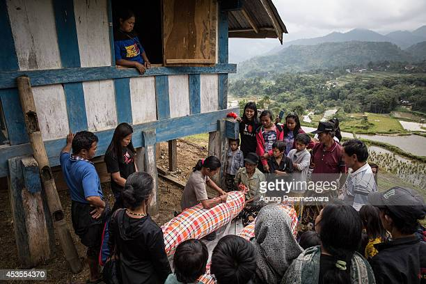 Family members cover bodies of deceased by clothes during Manene ritual on August 13 2014 in Toraja South Sulawesi Indonesia The Manene ritual...