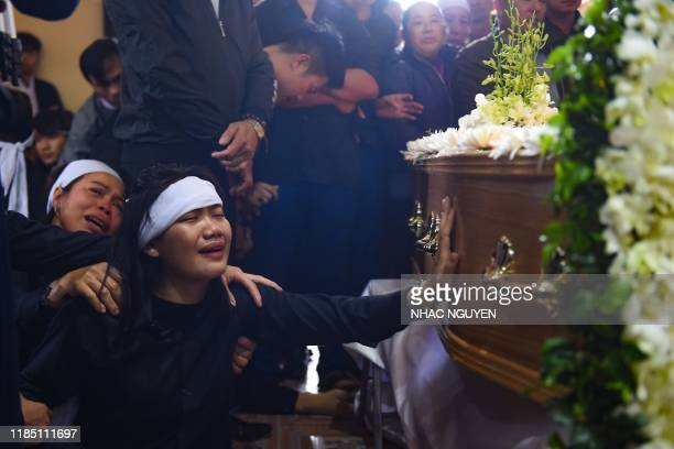 Family members cry before the coffin bearing the remains of Nguyen Van Hung during a funeral service at a church in Dien Chau district Nghe An...