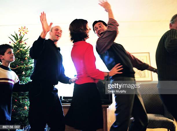 Family members dancing in 'conga' line, laughing