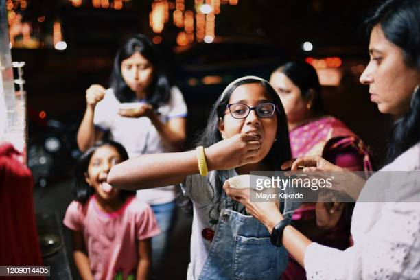 family members eating street food in the night - indian culture stock pictures, royalty-free photos & images