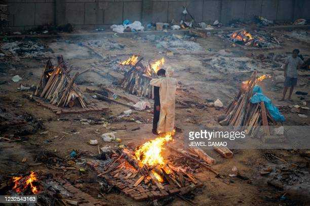 Family members embrace each other amid burning pyres of victims who lost their lives due to the Covid-19 coronavirus at a cremation ground in New...