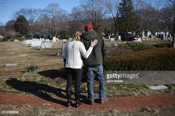 Family members embrace in a cemetery on March 6 2016 in Plantsville Connecticut to commemorate the first anniversary of the fatal heroin overdose of...