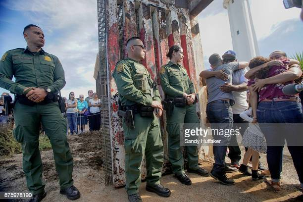 family members embrace their loved ones during a reunification visit through a gate along the US Mexico border November 18 2017 in San Ysidro...