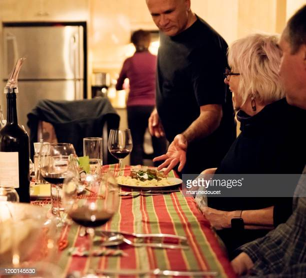 """family members enjoying a meal together. - """"martine doucet"""" or martinedoucet stock pictures, royalty-free photos & images"""