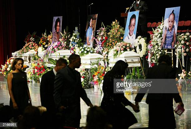 Family members file past four caskets bearing the remains of five other family members who were found shot to death in their home last week July 16...