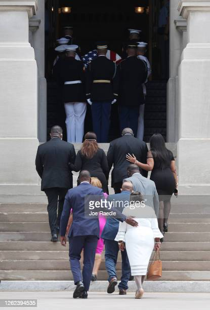 Family members follow behind as members of the joint services military honor guard carry the casket of Rep. John Lewis into the Georgia State Capitol...