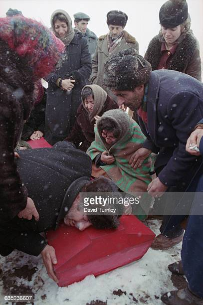 Family members grieve around the red coffin of a child killed in the major earthquake that shattered Armenia in December 1988 More than 25000 people...