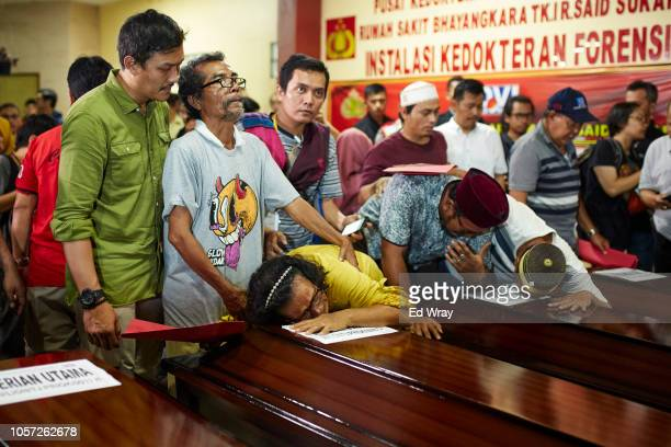 Family members grieve over a coffin of a relative after police handed over the remains of their relatives who died in the Lion Air flight JT 610...
