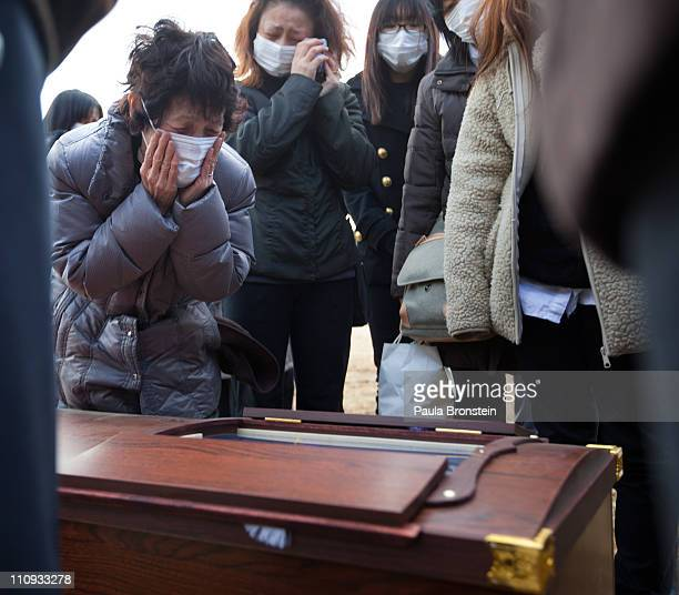Family members grieve over the coffin of Masami Takahashi during a burial service at a temporary burial site March 27 2011 in Kesennuma Miyagi Japan...