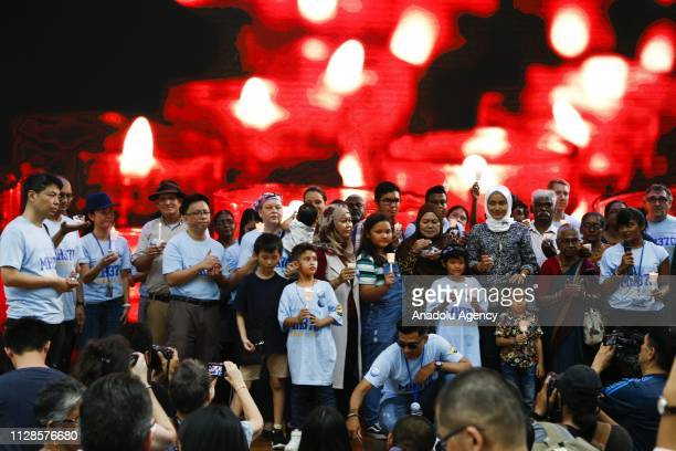 Family members hold a candles to pay tribute to missing passengers during a commemoration event to mark the 5th anniversary of the missing Malaysia...