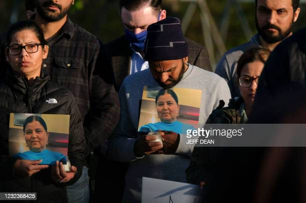 Family members hold a photo of their loved one during a candlelight vigil in Krannert Park in Indianapolis, Indiana, April 17 to remember the victims...