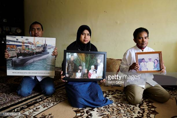 Family members hold photographs of Marine Colonel Harry Setiawan, commander of the Navy's KRI Nanggala submarine that went missing off the coast of...