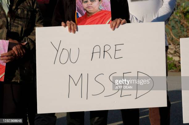 Family members hold photos and signs during a candlelight vigil in Krannert Park in Indianapolis, Indiana, April 17 to remember the victims of a mass...
