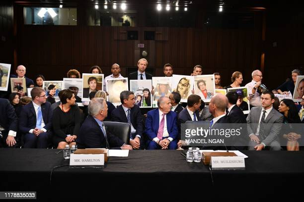 Family members hold up photos of loved ones they lost, as John Hamilton, vice president and chief engineer of Boeing Commercial Airplanes and Dennis...
