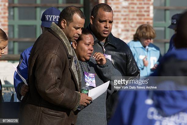 Family members huddle together during a prayer service for victims of the crash of American Airlines Flight 587 on boardwalk of Jacob Riis Park in...