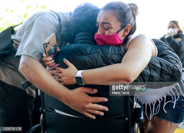 Family members hug Isaias Perez Yanez as Isaias is released from Sharp Coronado Hospital after battling COVID19 for five weeks there on May 8 2020 in...