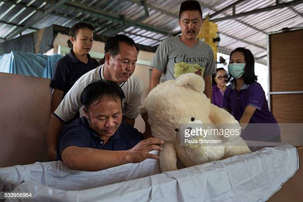 Family members identify the burnt body of Chomphu age 8 after DNA tests were completed placing a teddy bear in her coffin in Wiang Papao Chiang Rai...