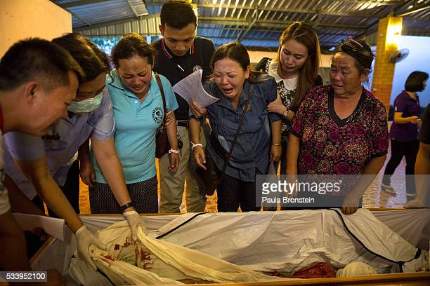 Family members identify the burnt body of Kanjanaporn Lasasong age 8 after DNA tests were completed in Wiang Papao Chiang Rai province May 24 2016 A...