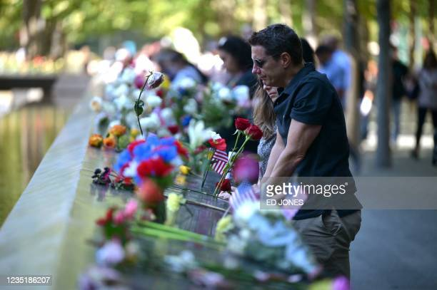 Family members leave flowers at the National 9/11 Memorial and Museum after the ceremony marking the 20th anniversary of the 9/11 attacks on the...